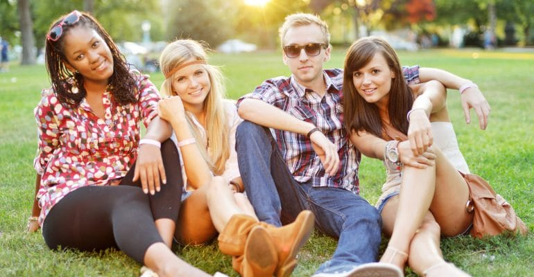 Young beautiful college students sitting together on the grass for a picnic.