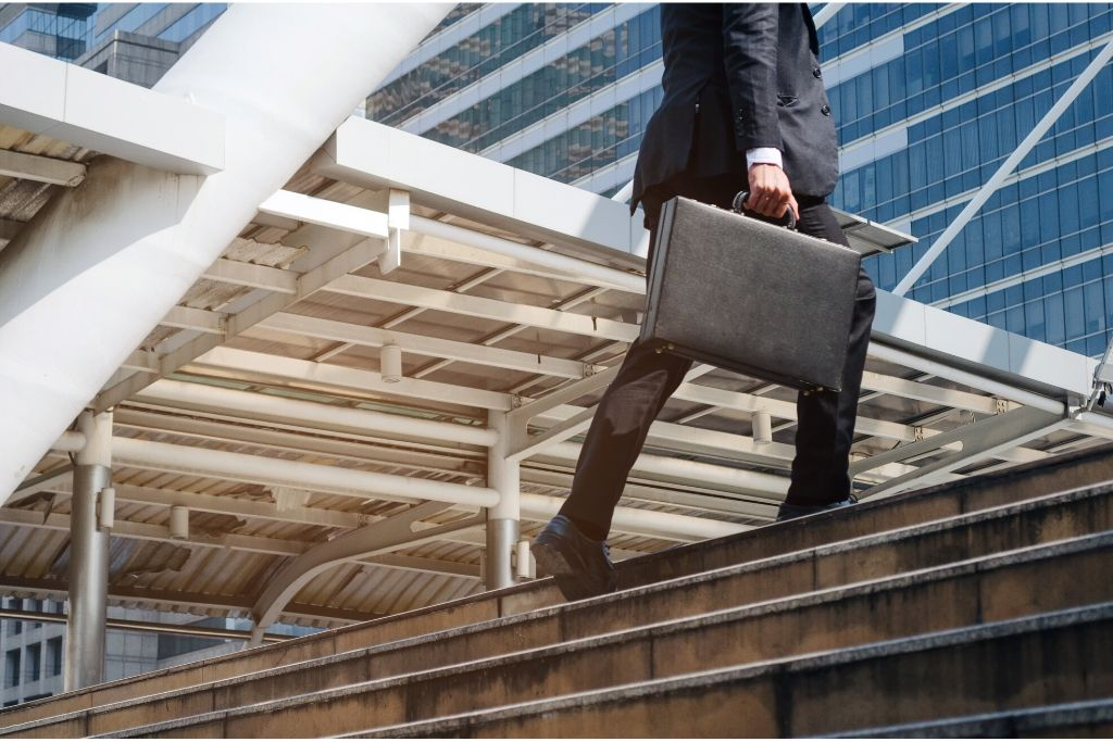 A young man with a briefcase climbs stairs to an office building