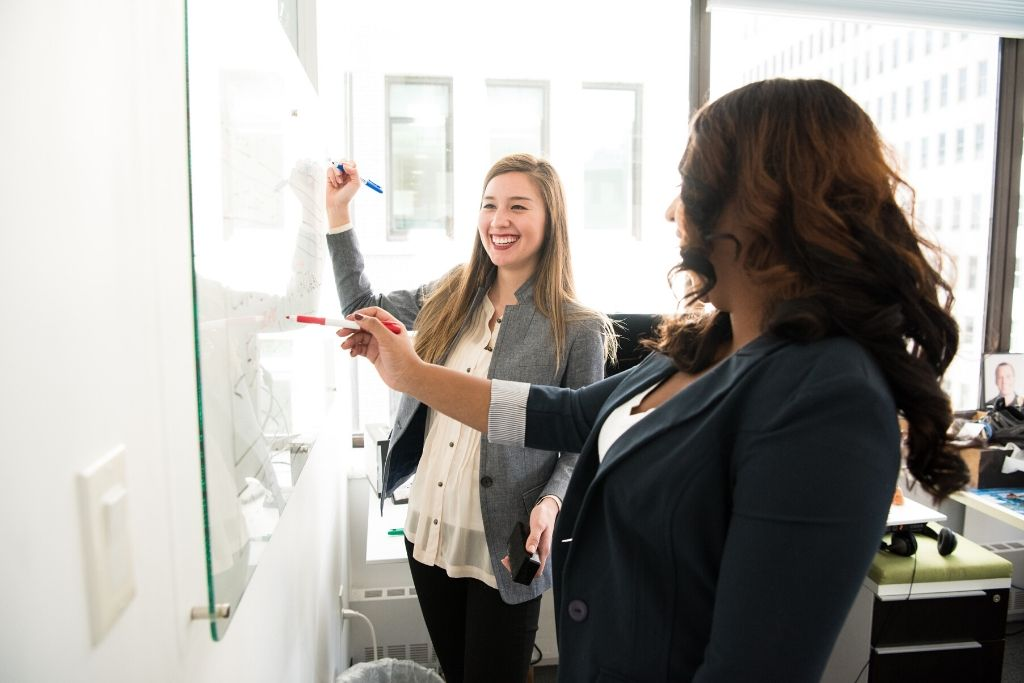 Two female students stand in front of a dry erase board