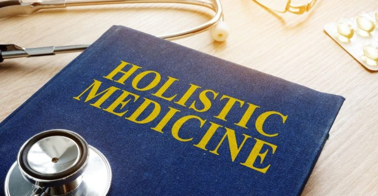 Holistic medicine book with a stethoscope on a desk.