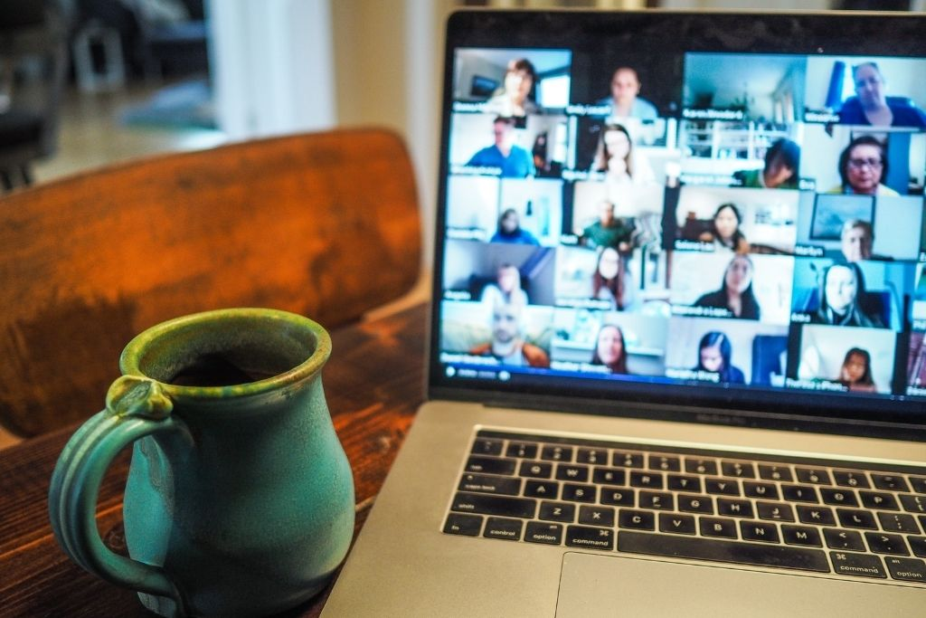 A laptop sitting next to a cup of coffee shows an online meeting platform