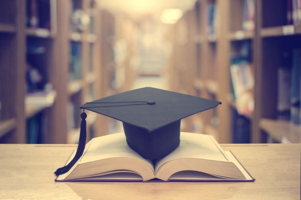 Library with books and a graduation cap.
