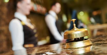 A service bell sits on a marble reception desk at a hotel