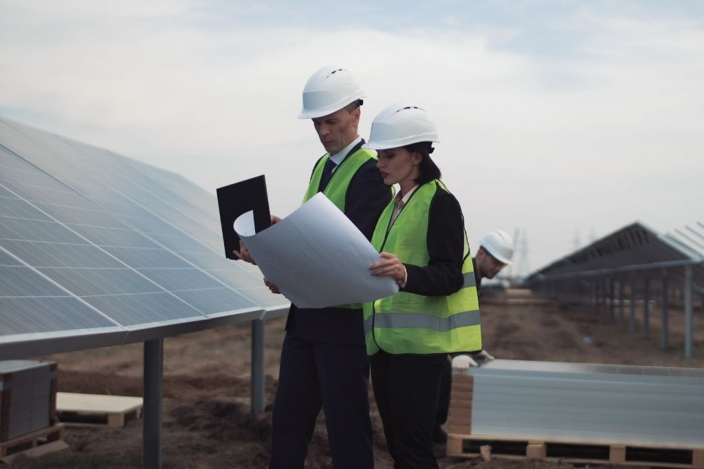 A male and female solar project manager look over plans on a solar farm
