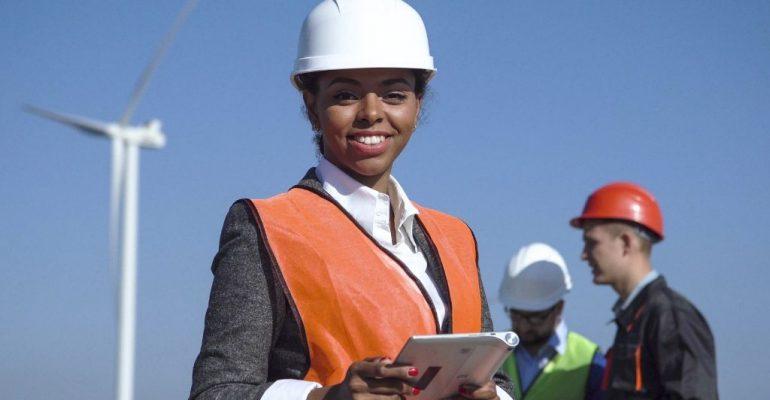 A female renewable energy graduate works on a wind farm
