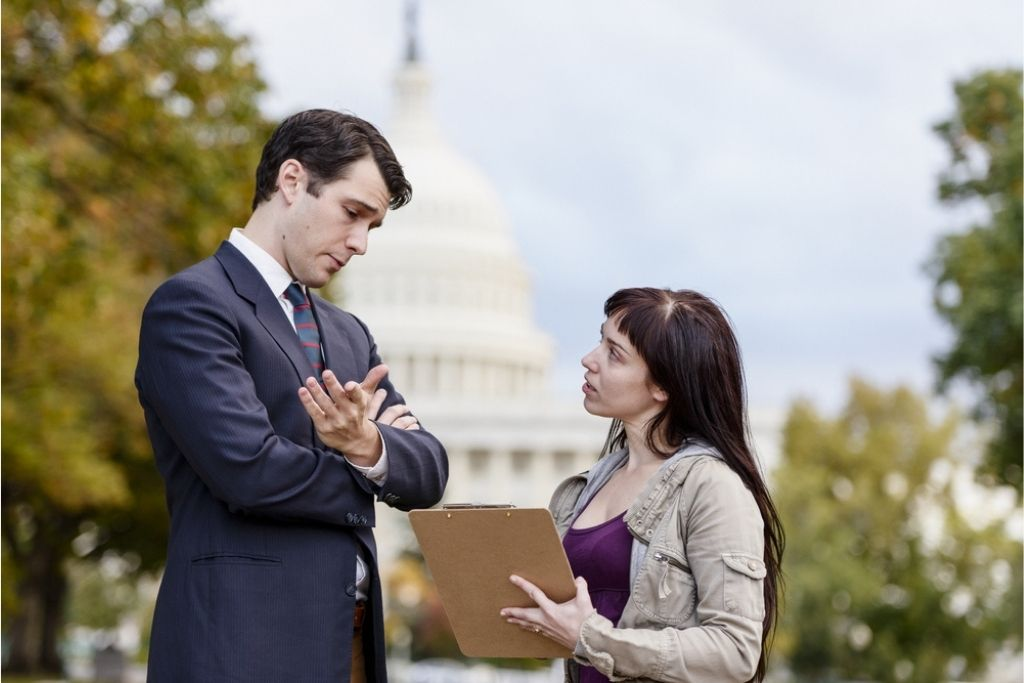 An environmental lobbyist speaks to a politician outside the capitol