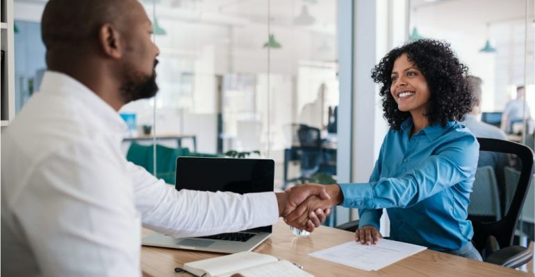 A male HR manager shakes the hand of a smiling female employee