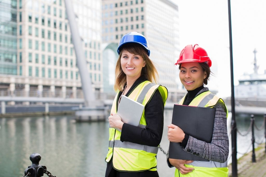 Two female construction management students hold tablets while working on a job site.