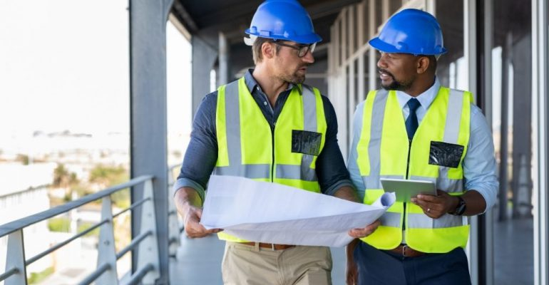 Two male construction managers discuss blueprints on a job site.