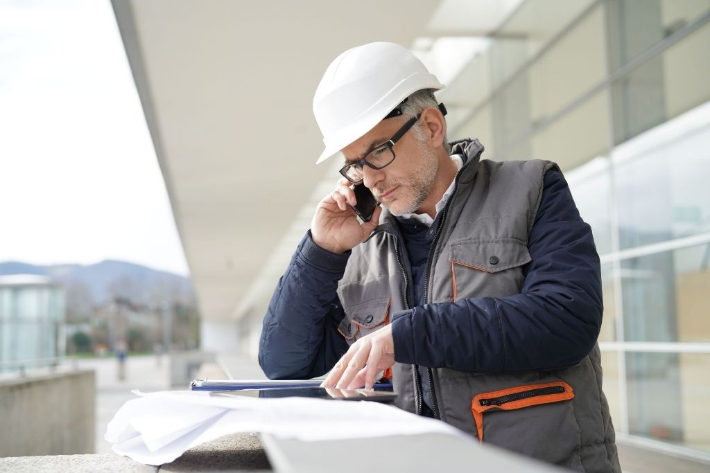 An older male construction manager overlooks plans while talking on a cell phone at the job site.