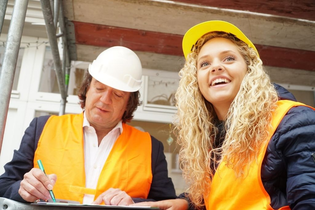 An older male construction manager works with a young female student on the job site
