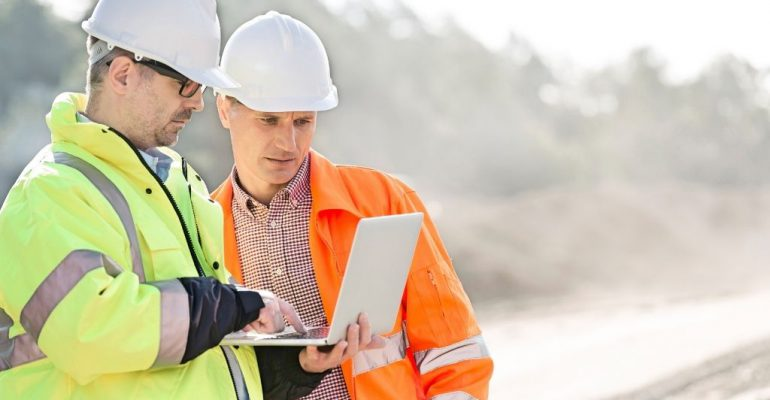 Two male construction managers looking at a laptop