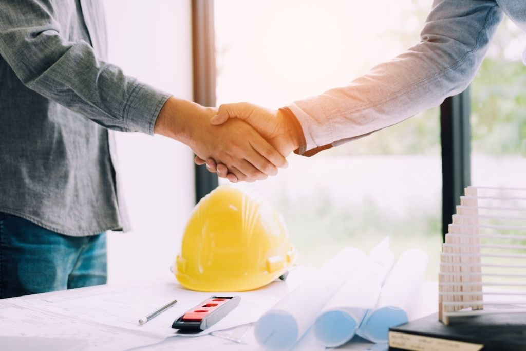A newly hired construction manager shakes hands with an employer at an interview
