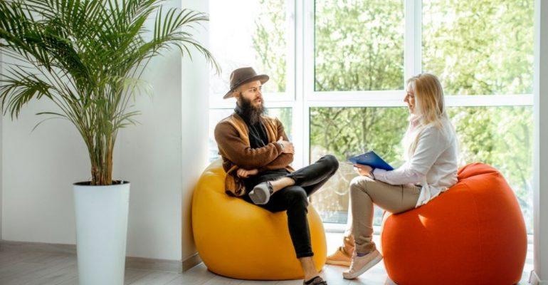 A female health coach sits on a bean bag chair while talking with a male client.