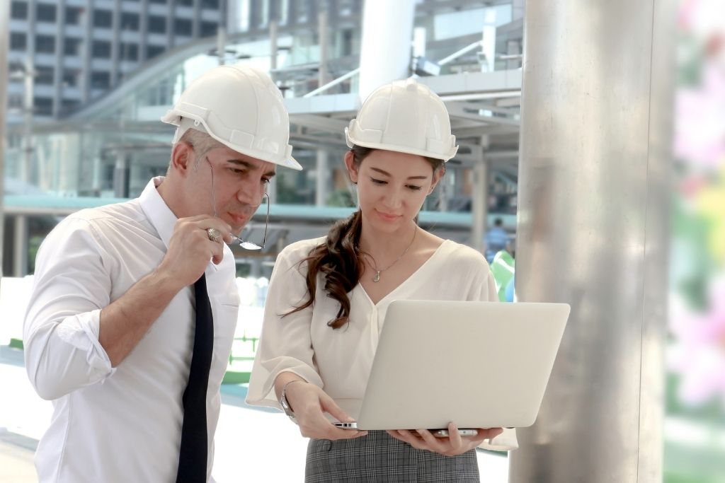 Man and woman in hardhats looking at a laptop on a construction site.