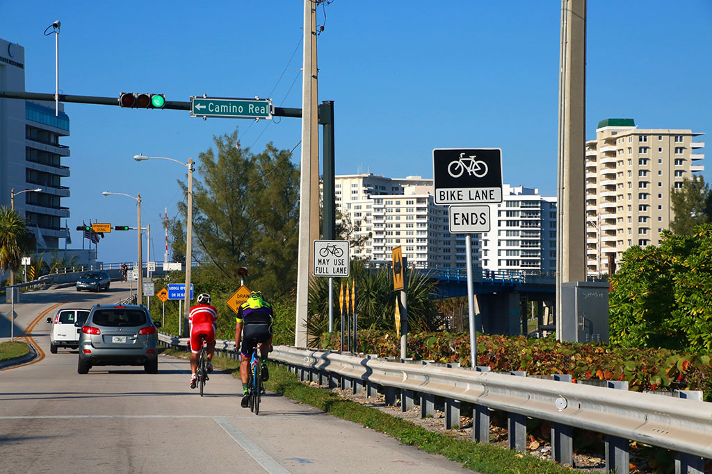 Two men cycle behind a car in Boca Raton