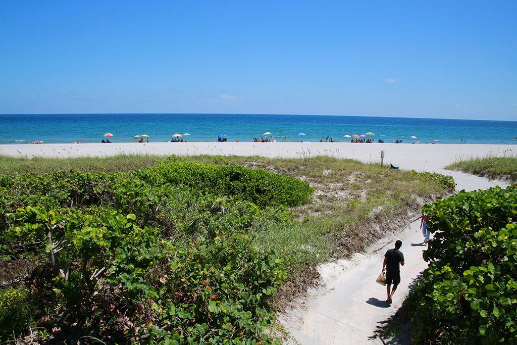 A man walks down a sandy path to Spanish River Beach Park in Boca Raton, Florida