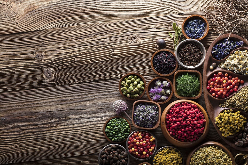 An assortment of herbs, seeds, fruits, and vegetables on a wooden table