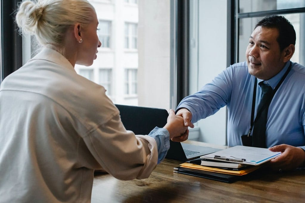 An older male human resource manager shakes hands with a young female at a job interview.