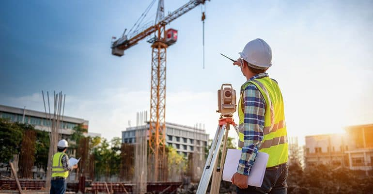 Man using survey equipment on a construction site.
