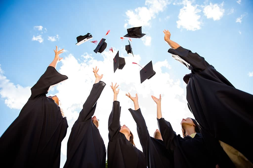 Students after graduation throwing their graduation hats in the air.