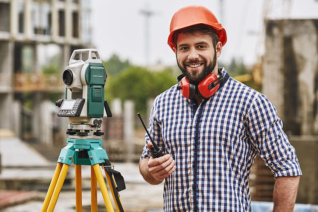 Man with a hard hat and protective gear on a construction site within the Surveying Industry