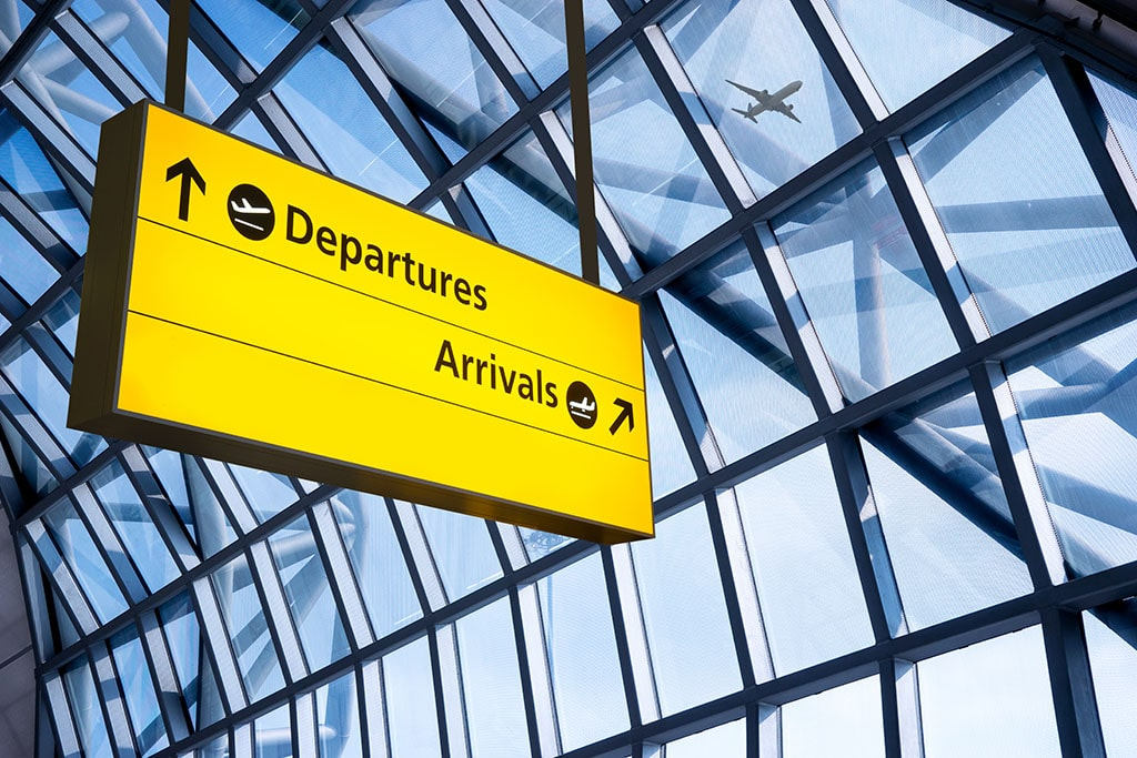 Large yellow airport sign for departures and arrivals with a glass background.