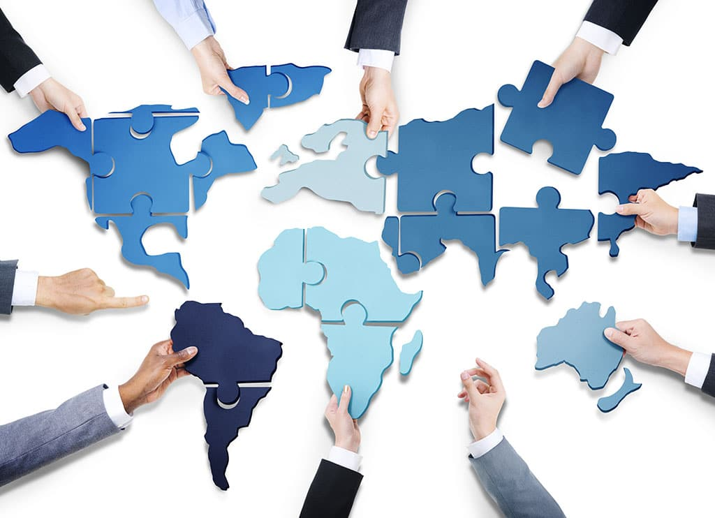 A group of hands all holding blue pieces of the globe that fit together if they work as a team.