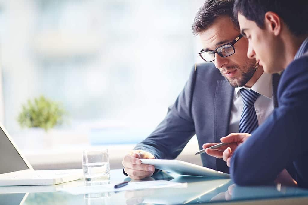 Two businessmen talk while looking over an iPad with a laptop in the background.