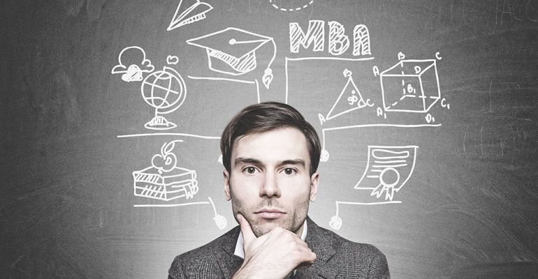 A young man stands in front of a chalkboard with ideas about what you can do with an MBA.