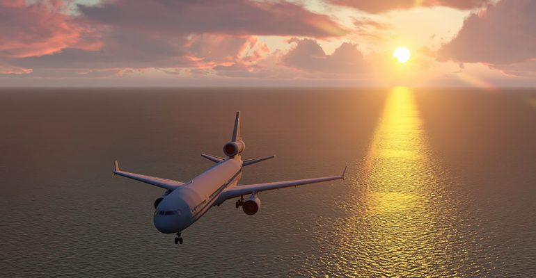 Airplane flying over water during a sunset.