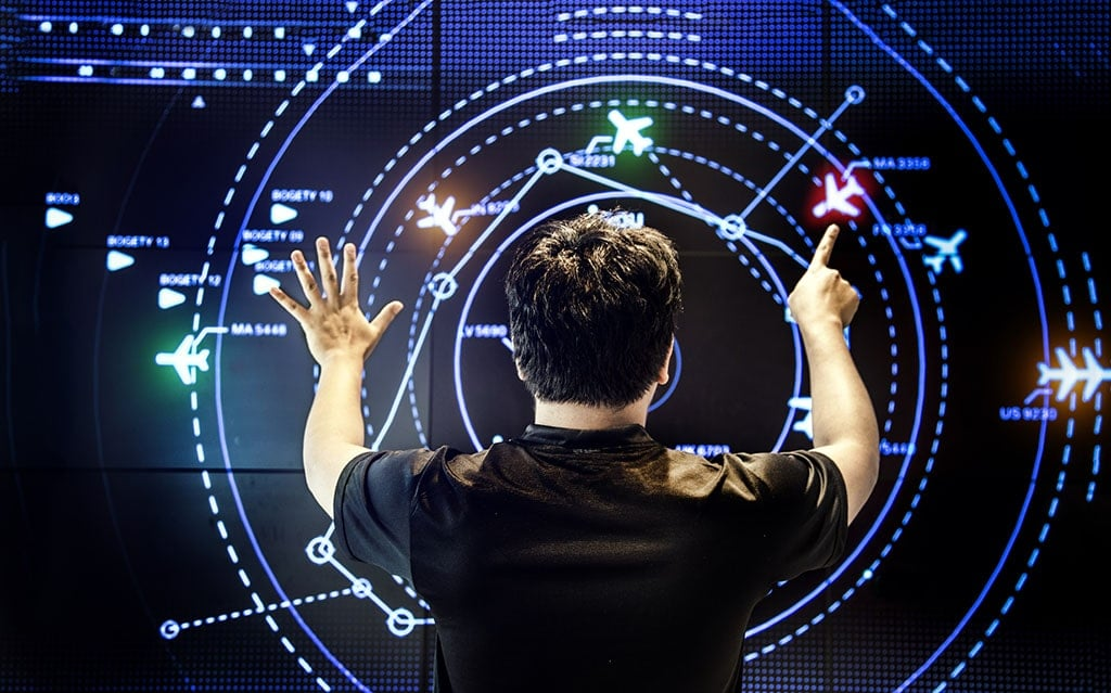View of the back of a man controlling an aviation map as he navigates a screen with moving detect technology