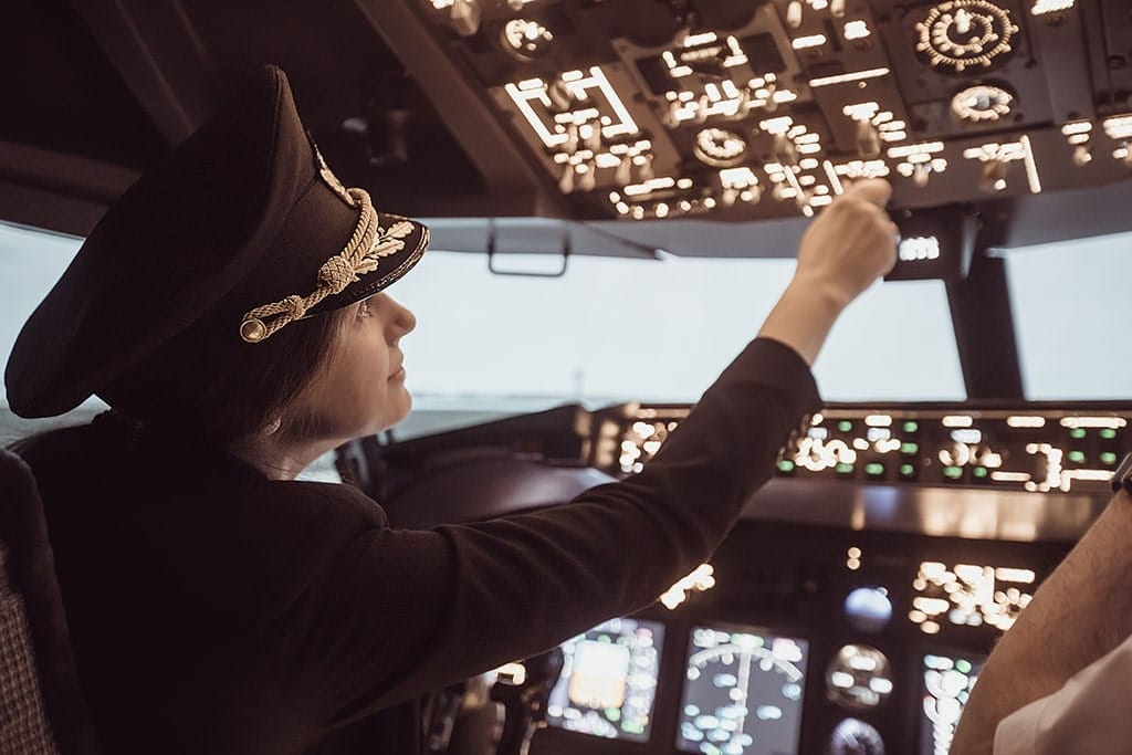 Uniformed female pilot within the plane prepares for take-off in the plane cockpit.