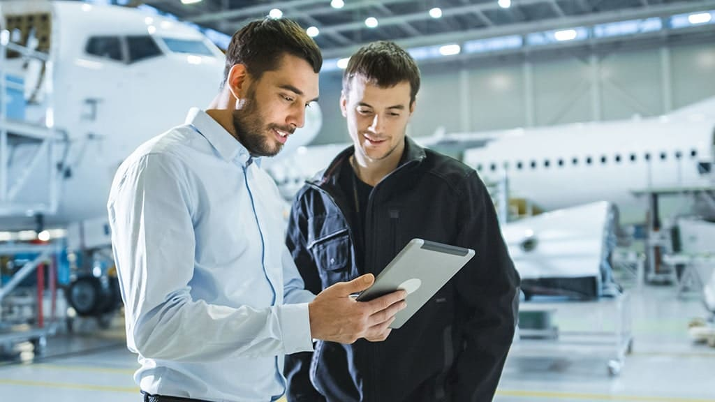 Aircraft Maintenance Worker and Engineer having Conversation while talking on a tablet