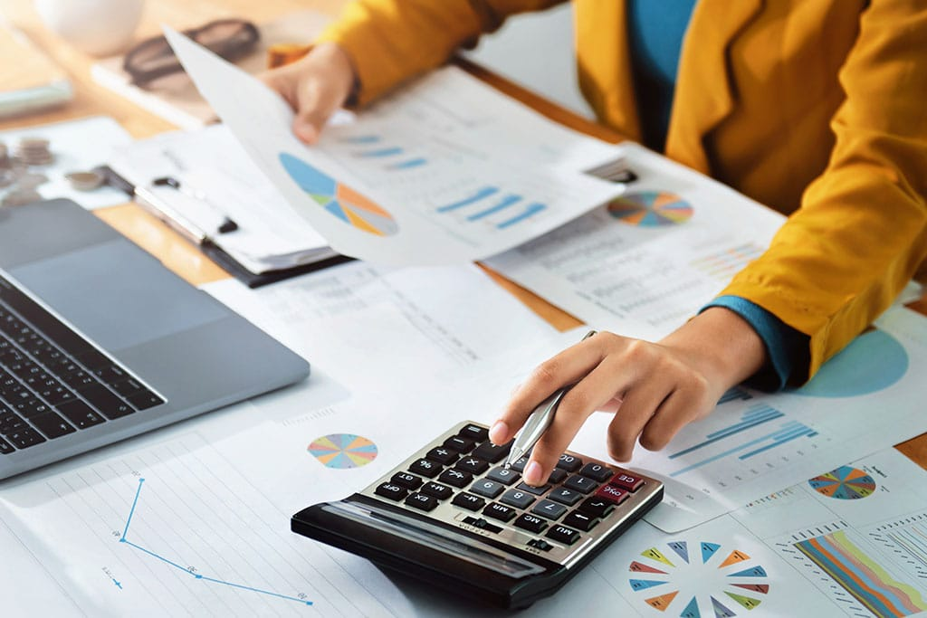 Woman does calculations while looking at financial reports and graphs.