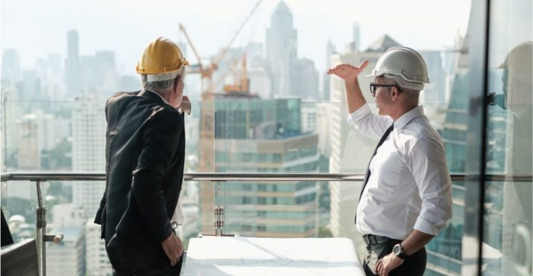 A construction manager discussing a project with his colleague at a construction site.