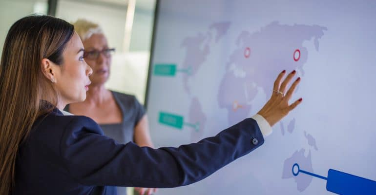 A woman doing a business presentation with a screen showing a map of the world.
